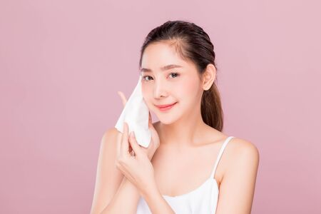 Young attractive Asian woman using hygiene wiper sheet to clean her face skin isolated on pink background.