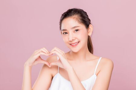 Young attractive Asian woman with smiley face making heart shape by her hands isolated on pink background.