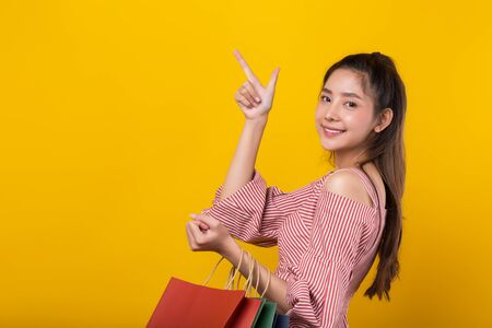 Young happy Asian woman holding shopping bags with smiley face pointing to the copy space isolated on yellow background.
