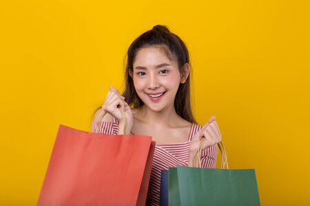 Young happy Asian woman holding shopping bags with smiley face isolated on yellow background.