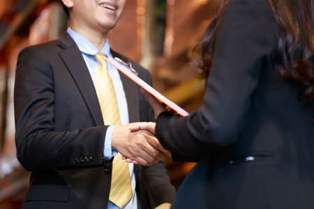 Close up cropped Asian businessman hand shaking teethe smile with business woman, dealing investing business concept.