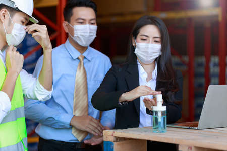Portrait of attractive Asian businessman and investor woman, engineer, wearing protective face mask using alcohol cleansing hands, new normal after Covid-19 Corona virus pandemic. 스톡 콘텐츠