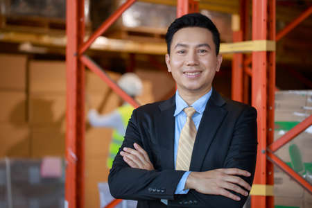 Portrait of asian business man owner company in black formal suit standing with confident crossing his arms on warehouse factory background, Business Investor concept.