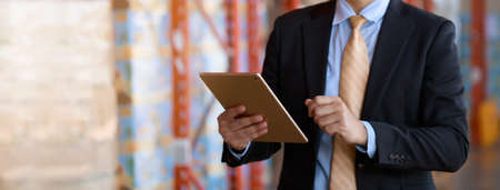 Close up businessman in black suit investor using tablet checking inventory in warehouse industry, panorama banner size.