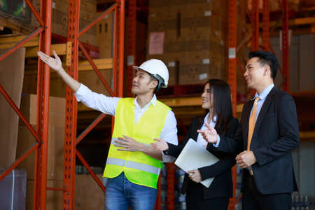 Asian Warehouse manager and male worker as engineer interacting talking checking inventory, manager team working at the storehouse. 스톡 콘텐츠