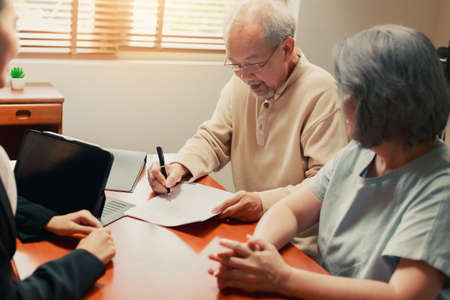Happy Asian senior couple feel releif and pleasant after get the advice about family financial planning from professional financial advisor at home. Foto de archivo