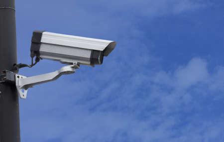 Security  surveillance camera against a clear blue sky photo