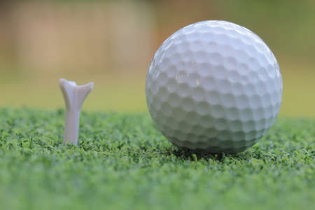 Golf ball on tee. Green grass photo