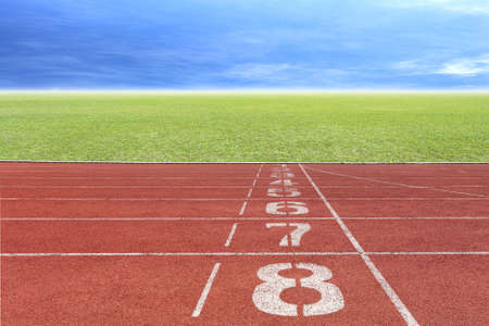 Running track number in front of tracks and stadium with blue sky and white cloud. Stock Photo