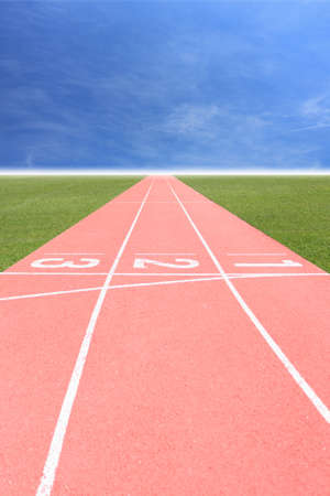 Running track number in front of tracks with blue sky and white cloud. photo