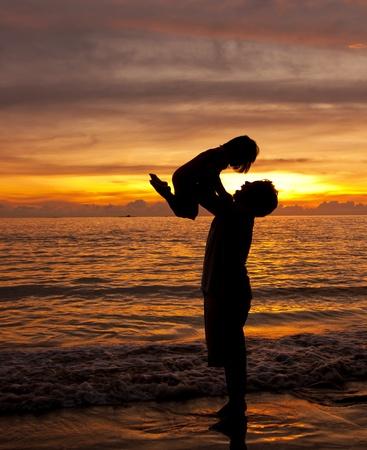 Vader en dochtertje silhouetten op het strand bij zonsondergang