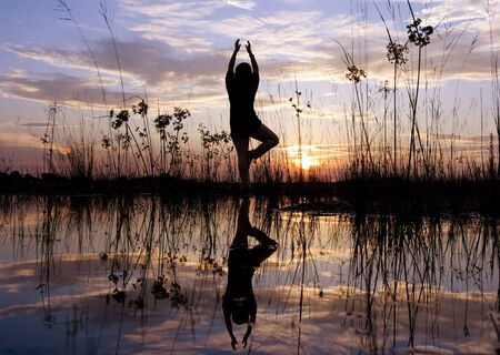 Women silhouette doing yoga pose with dramatic sunset sky background Stock Photo