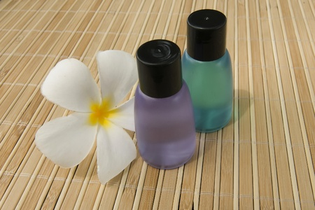 Spa Concept: bottles of lotion, flower on bamboo matte