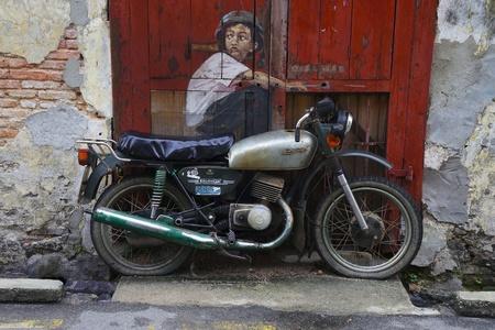 Penang, Maleisië-14 februari: Algemeen beeld van een muurschildering 'Jongen op een fiets' geschilderd door Ernest Zacharevic in Penang op Feb.14, 2012. Het werd geschilderd zijn figuur tekeningen en portraitures dat de uitbundigheid van het leven in de binnenstad vieren.