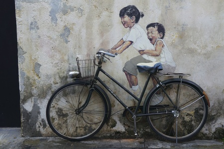 PENANG, MALAYSIA-FEB 14: General view of a mural 'Little Children on a Bicycle' painted by Ernest Zacharevic in Penang on Feb.14, 2012. The mural is one of the 9 murals paintings in early 2012.