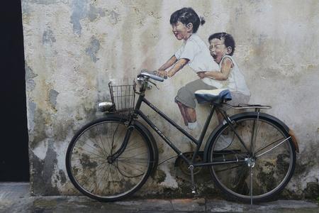 Penang, Maleisië-FEB 14: Algemeen beeld van een muurschildering 'Little Children op een fiets', geschilderd door Ernest Zacharevic in Penang op Feb.14, 2012. De muurschildering is een van de 9 muurschilderingen schilderijen in het begin van 2012. Redactioneel