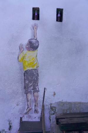 PENANG, MALAYSIA-DEC.9: Street Mural entitled Reaching Up painted by Ernest Zacharevic in Penang on Dec.9, 2012. It was painted in conjunction with the 2012 George Town Festival.