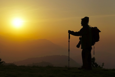 Hiker on top, silhouetted in high mountains at sunrise                                Stock Photo