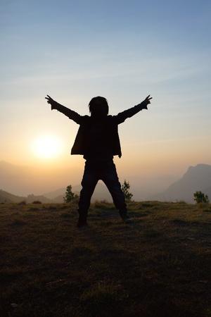 Silhouet van de man show vredesteken in het hooggebergte tijdens zonsopgang