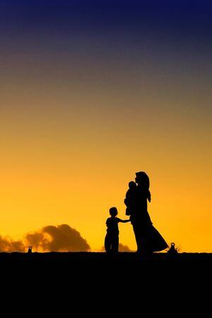 siluetas de mujeres: siluetas de una mujer con su hija durante el atardecer Foto de archivo