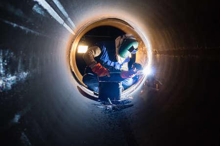 Workers welding work at night in the pipeline. Foto de archivo