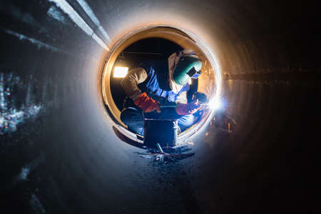 welding mask: Workers welding work at night in the pipeline. Stock Photo