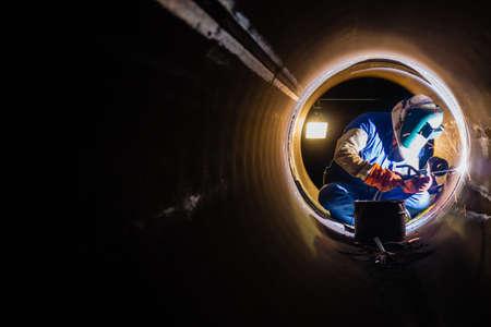 soldadura: Trabajadores trabajos de soldadura en la noche en la tuber�a.