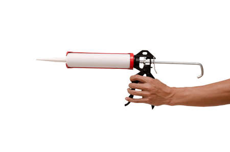 Men's hand holding Caulking gun and white silicone sealant