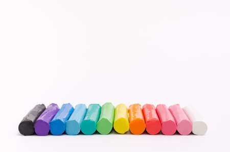Multi-colored modelling clay stacked on a white background.