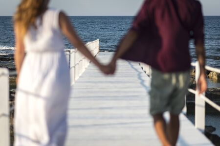 A couple strolls on a pier at sunset holding hands. she in a white dress and he in a red shirt and Bermuda shorts