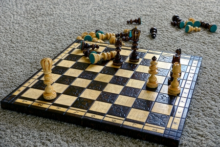 chess board: Chessboard with chess on a gray wool carpet Stock Photo