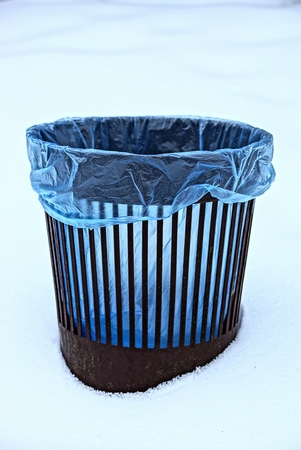 Brown plastic urn with blue garbage bag Stock Photo