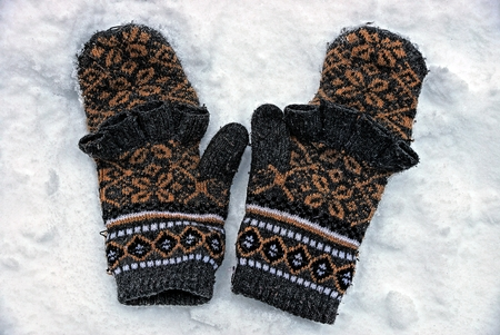 Pair of woolen mittens with a pattern on the snow