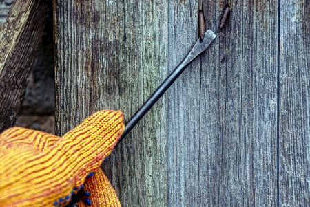 Screwdriver in hand and bent nail in a wooden wall Stock Photo