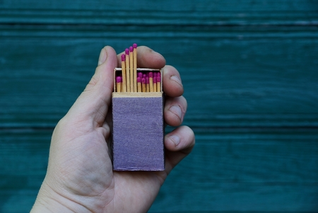 Box of matches in hand against the background of green wall