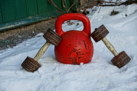 Red weights with dumbbells in the snow Stock Photo