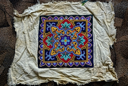 An old colored embroidered pattern on a piece of old cloth