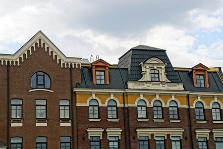 Part of apartment houses with roofs and windows against the sky