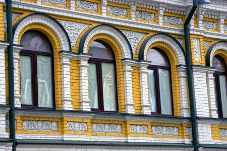 gutter: A row of windows on the brick facade of an old house