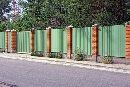 Recinzione verde e cancelli davanti alla strada asfaltata Archivio Fotografico - 80423366