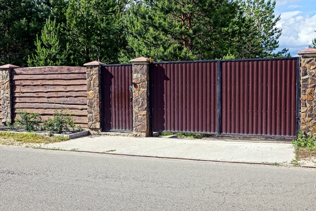 Gray brown iron gates and wooden fence in front of the asphalt road Stock Photo