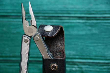 gripper: Iron pliers in a leather case on a green background