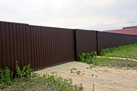 Brown iron gate and closed door on metal fence