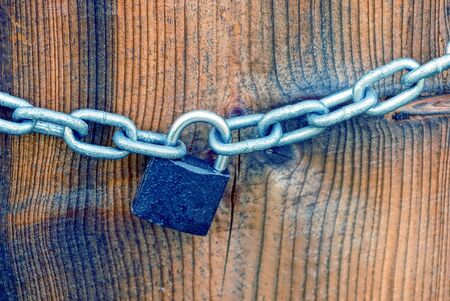 deterrence: Small iron lock and white chain on a brown board