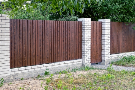 wicket door: Gray brown closed doors and a wooden fence in front of asphalt road Stock Photo