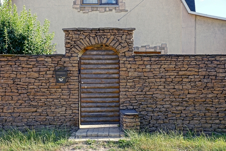 A gray stone fence and a wooden door with a mailbox on the wall Stock Photo