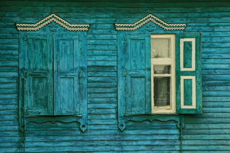 Two old windows with wooden shutters on the green wall of a rural house Stock Photo