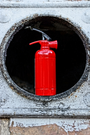 Small red fire extinguisher on a round hole heating boiler Stock Photo
