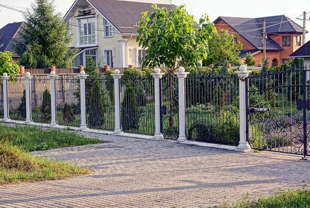 Black-white fence with a wicket in front of a private garden and a house on the street
