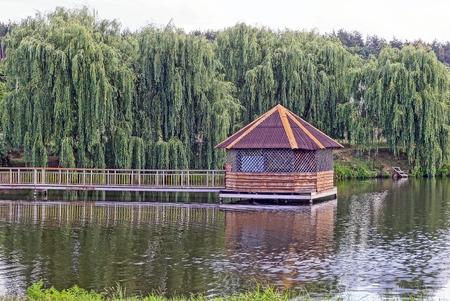 Houten huis aan het water met groene bomen op het strand Stockfoto